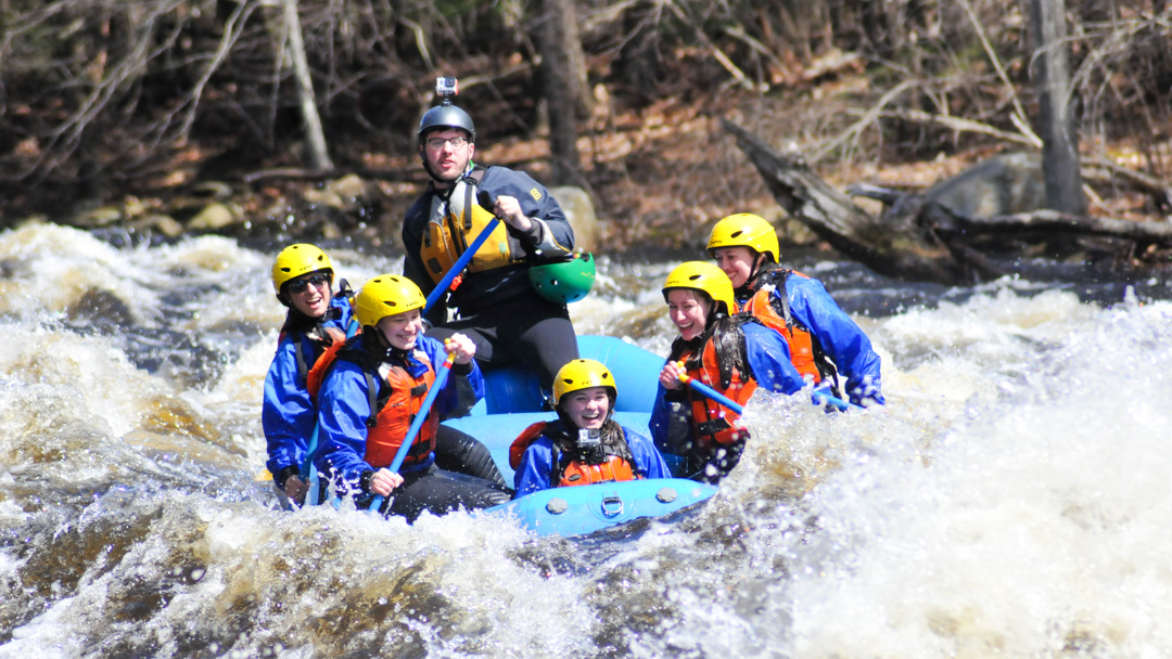 Group of young people rafting down Millers River