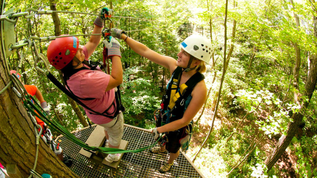 Zip-lining instructor helping a woman buckle in for a zip