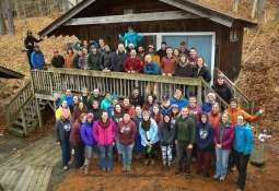 Zoar Outdoor staff taking a group photo outside on a porch