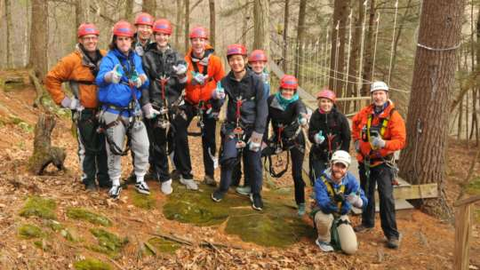 Group of zip liners taking a group photo in the woods