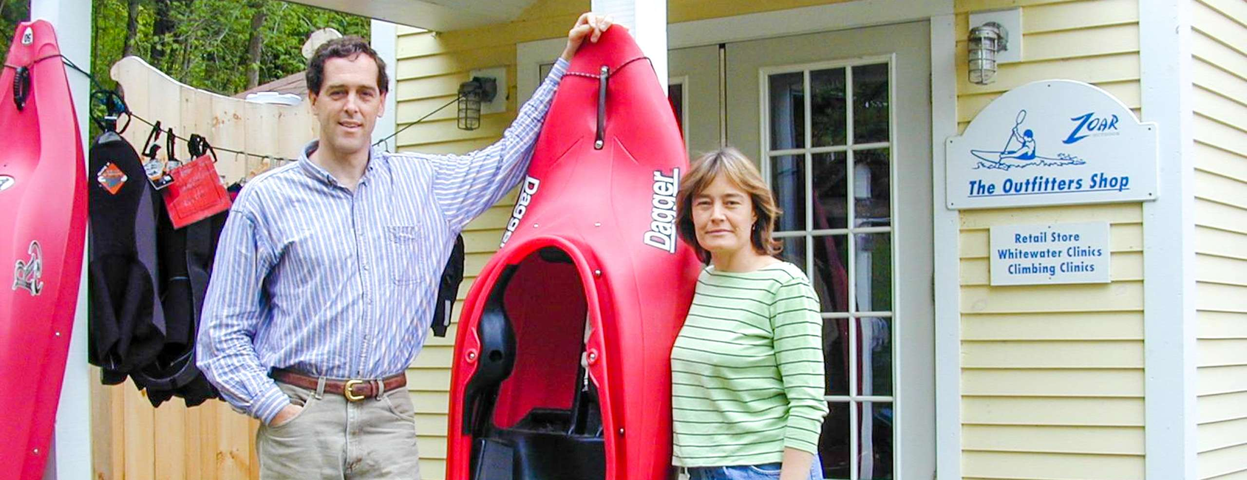 Founders Bruce and Karen standing by a kayak perched up against a house