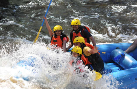 Group of people in a raft getting splashed by the rapids