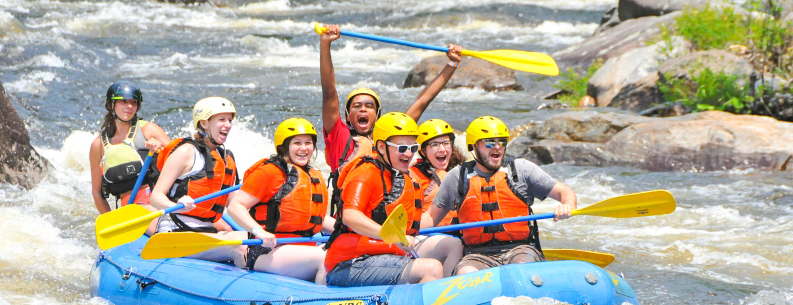 Group of people excitedly rafting on the river