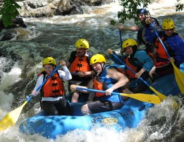 Group of people rafting down rapids