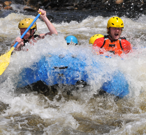 Group in a raft getting splashed by the rapids