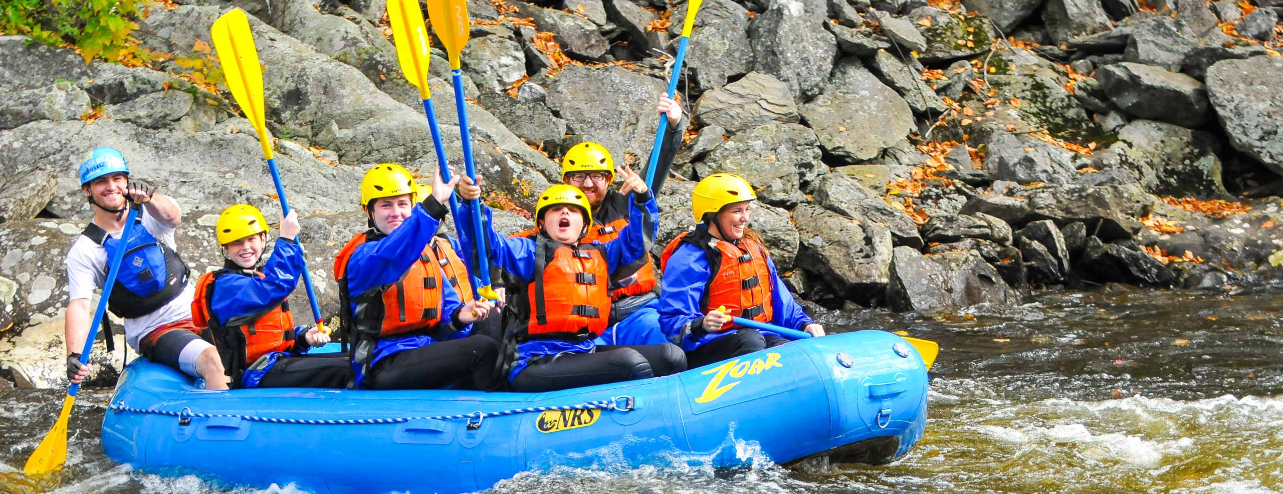 Family in a raft holding their oars in the air excited for their trip