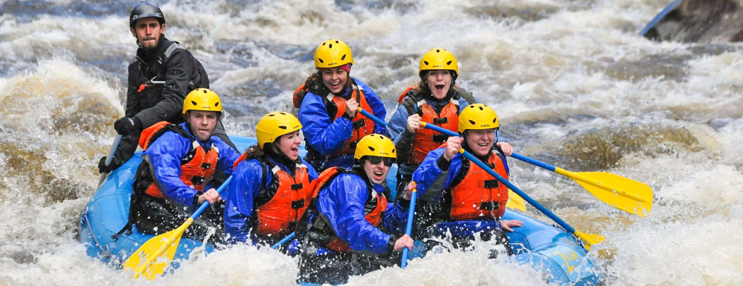 Group of people in a raft paddling during rapids