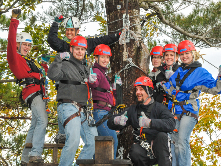 Group of people on a zip lining trip standing on a tree platform