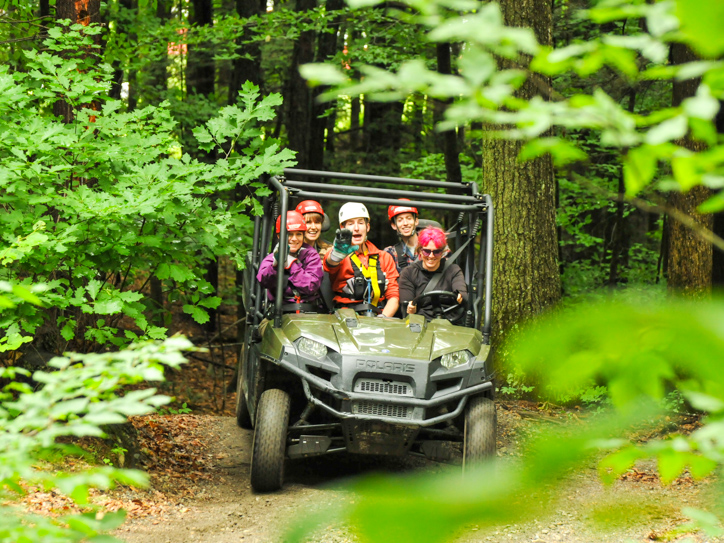 Group of people in an ATV driving through the forest