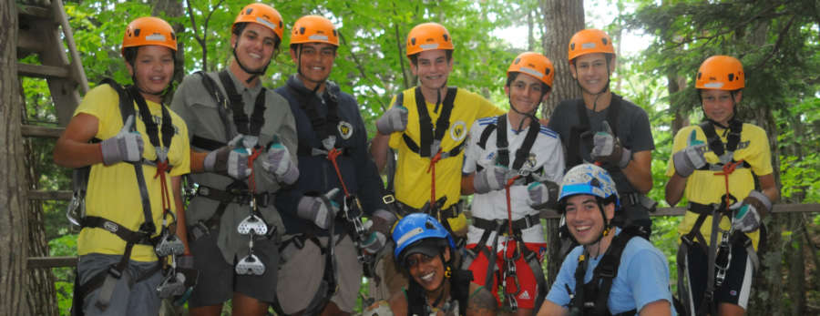 Group of boys and girl with zip lining helmet and harnesses ready to zipline