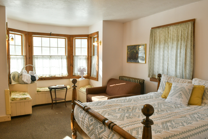 Hawk Mountain Lodge bedroom with bay window, chair, and queen bed