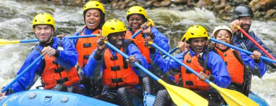 Group of people in a raft navigating rapids on Millers River