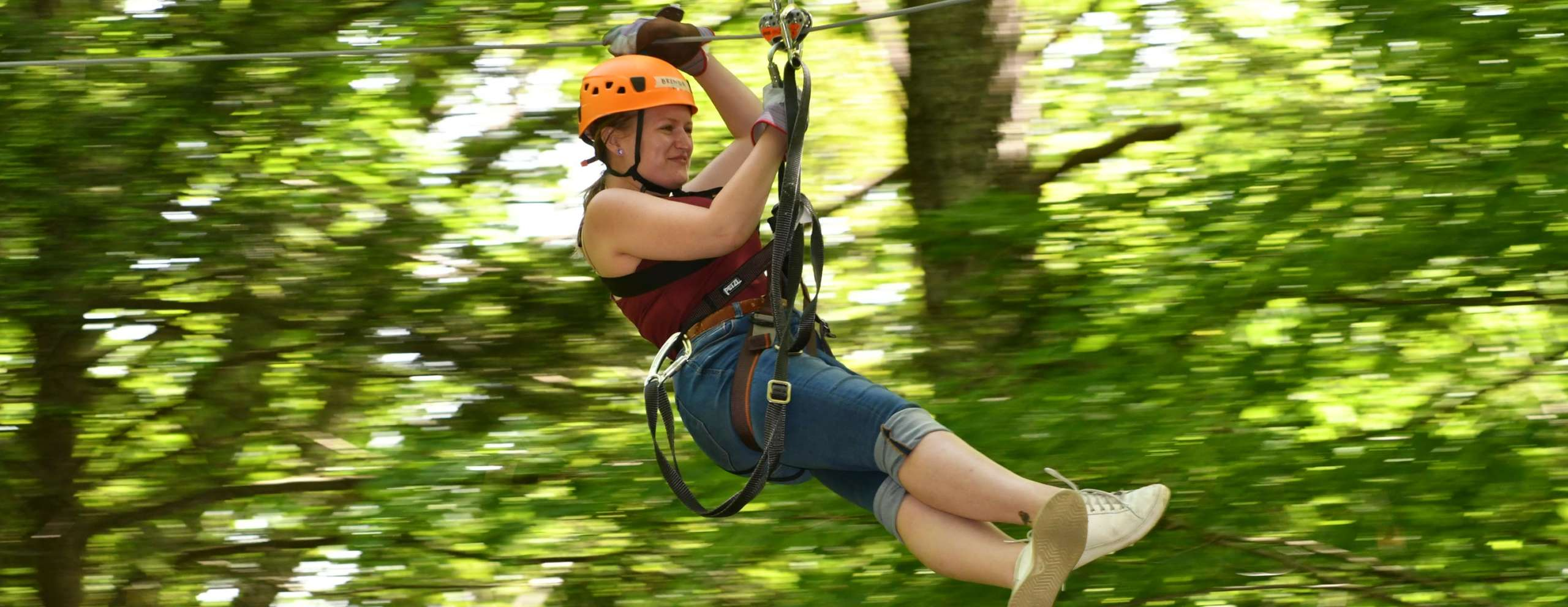 Woman zip lining through the canopy
