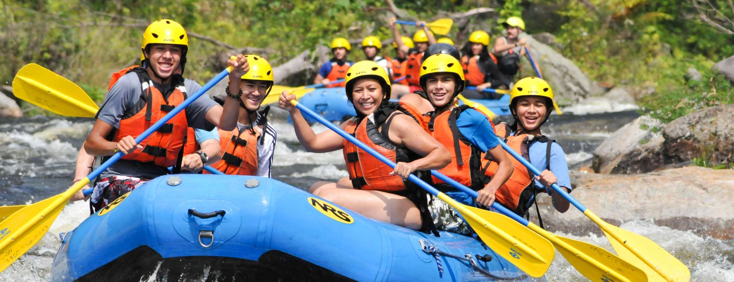Group of adults rafting down rapids