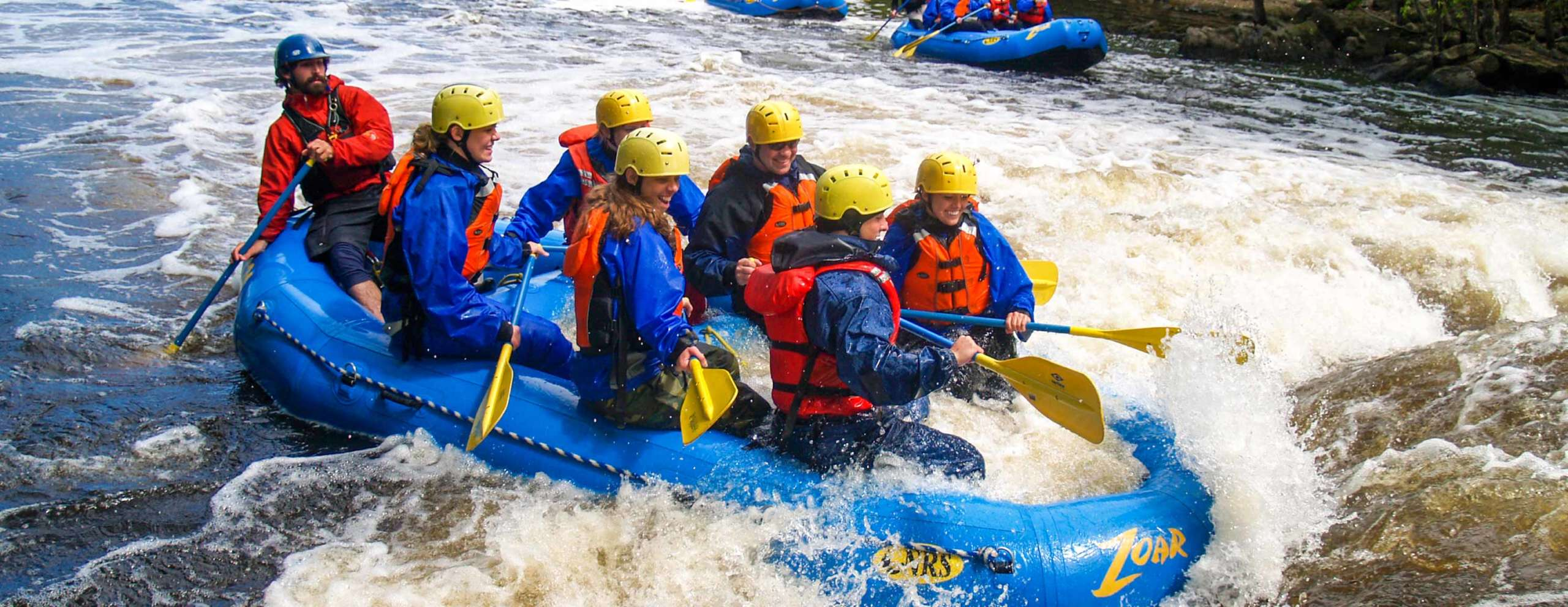 Group of people rafting in rapids