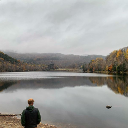 Man standing on shoreline looking out at the calm river surrounded by trees and mountains