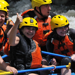 Boy giving a thumbs up as he rafts down the river