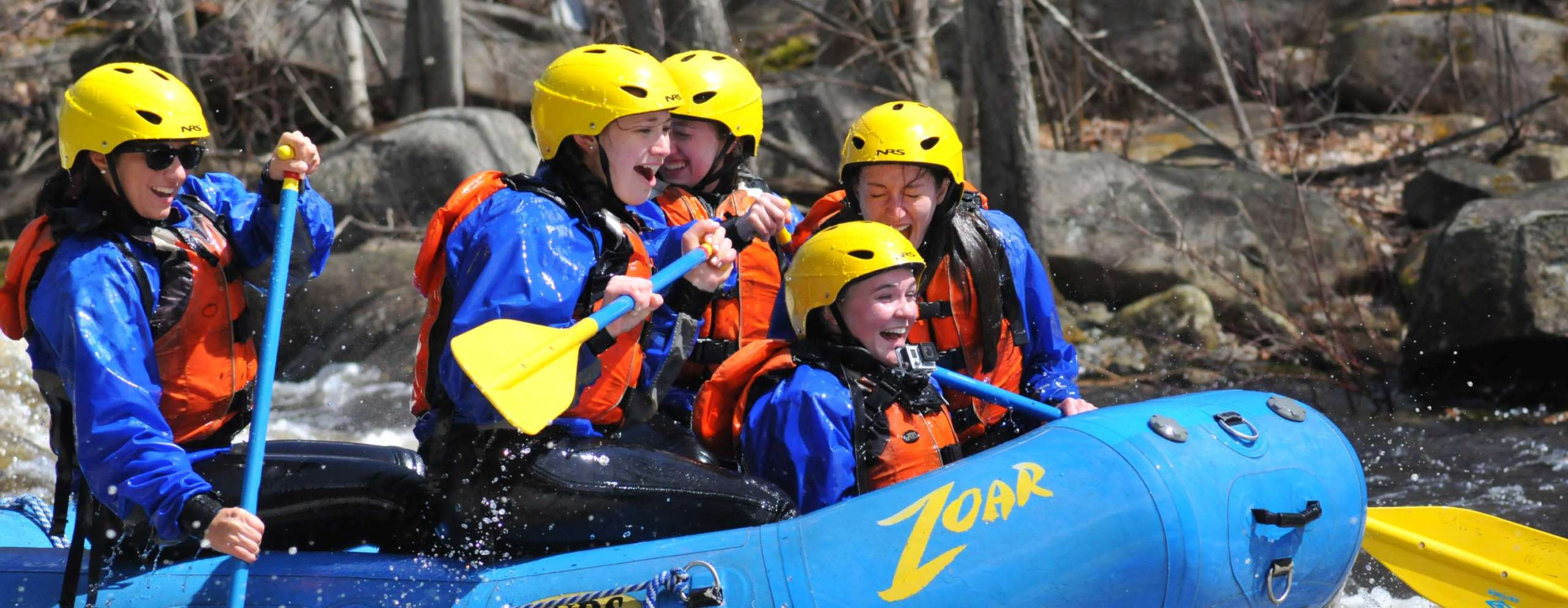 Rafting group having fun and smiling as they navigate rapids