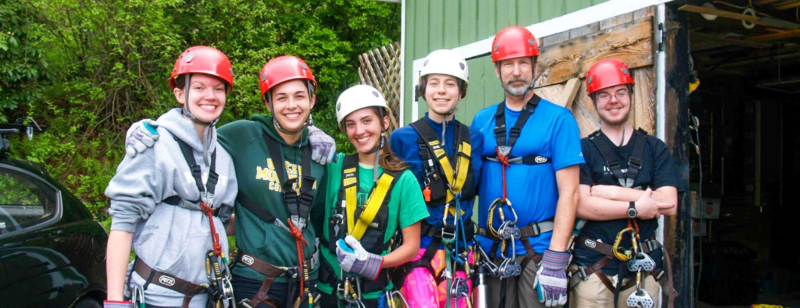 Group of people in zip lining gear taking a group photo