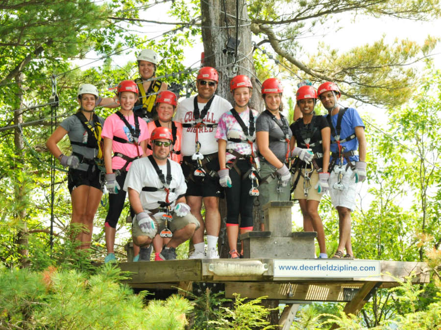 Group of people standing on a perch in the trees ready to zipline