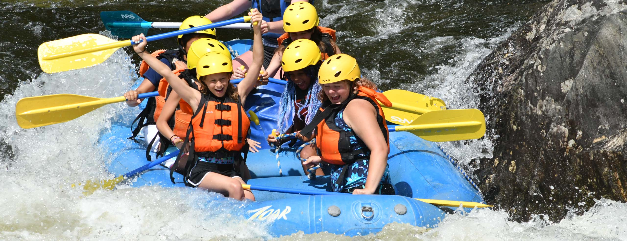 Group of girls excitedly rafting down the zoar gap