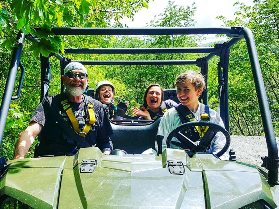 Four staff members in an ATV smiling together