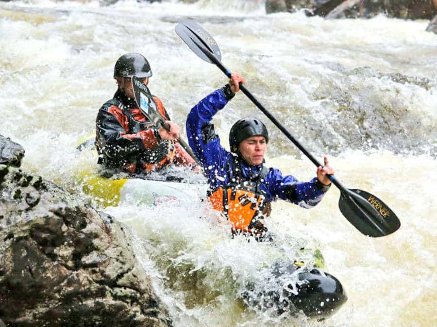 Two men kayaking through rough rapids