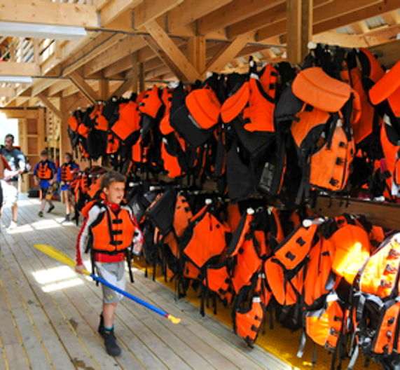 Child walking by all of the hanging life vests in equipment barn