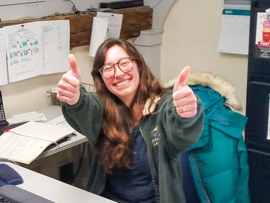 Staff member sitting in a cubicle giving two thumbs up