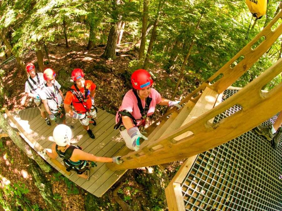 Zoar team member helping group members climb a ladder to a zip line platform
