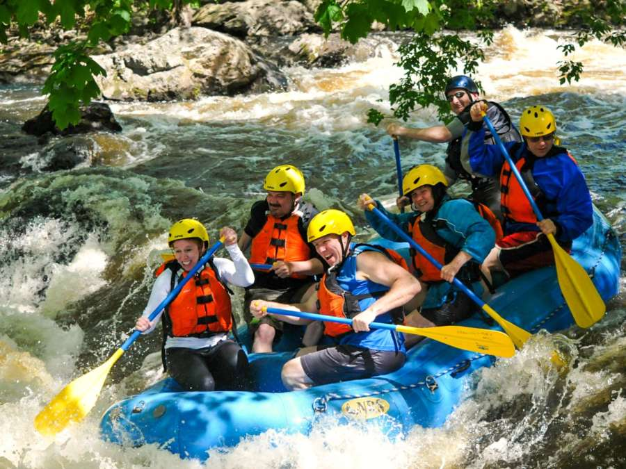 Group of people in a raft navigating small rapids