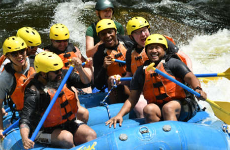 Group of people in a raft smiling and having fun paddling