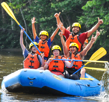 Group of young people in a raft with their oars and arms up looking excited