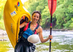 Shira Lander holding a kayak and paddle on a river bank