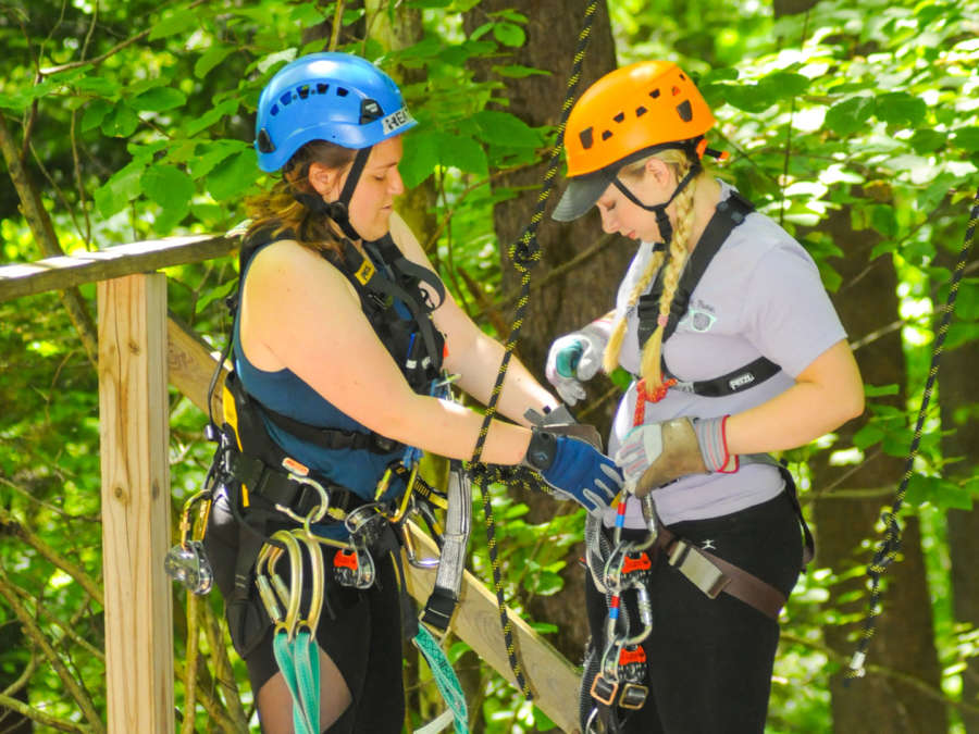 Staff member helping visitor get harness buckled properly for a zip line ride