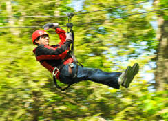 Man zip lining through the forest