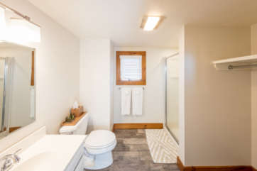 Bright white large bathroom with toilet, sink, bath shower, and closet