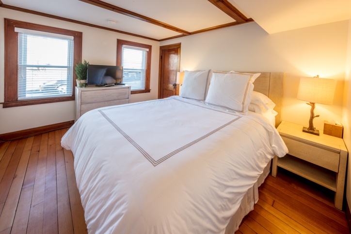 Bright white bedroom with hardwood floors and queen bed