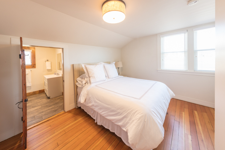 Bright white bedroom with hardwood floors and queen bed and attached bathroom