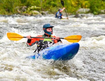 Man with helmet kayaking through rapids